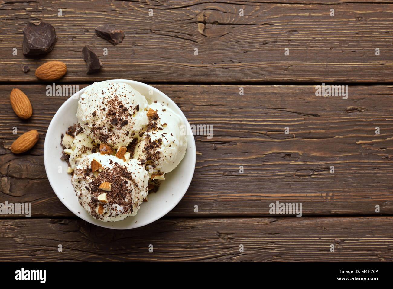 Leckere Schokolade Eis mit Muttern in die Schüssel auf Holz- Hintergrund mit kopieren. Ansicht von oben, flach Stockbild