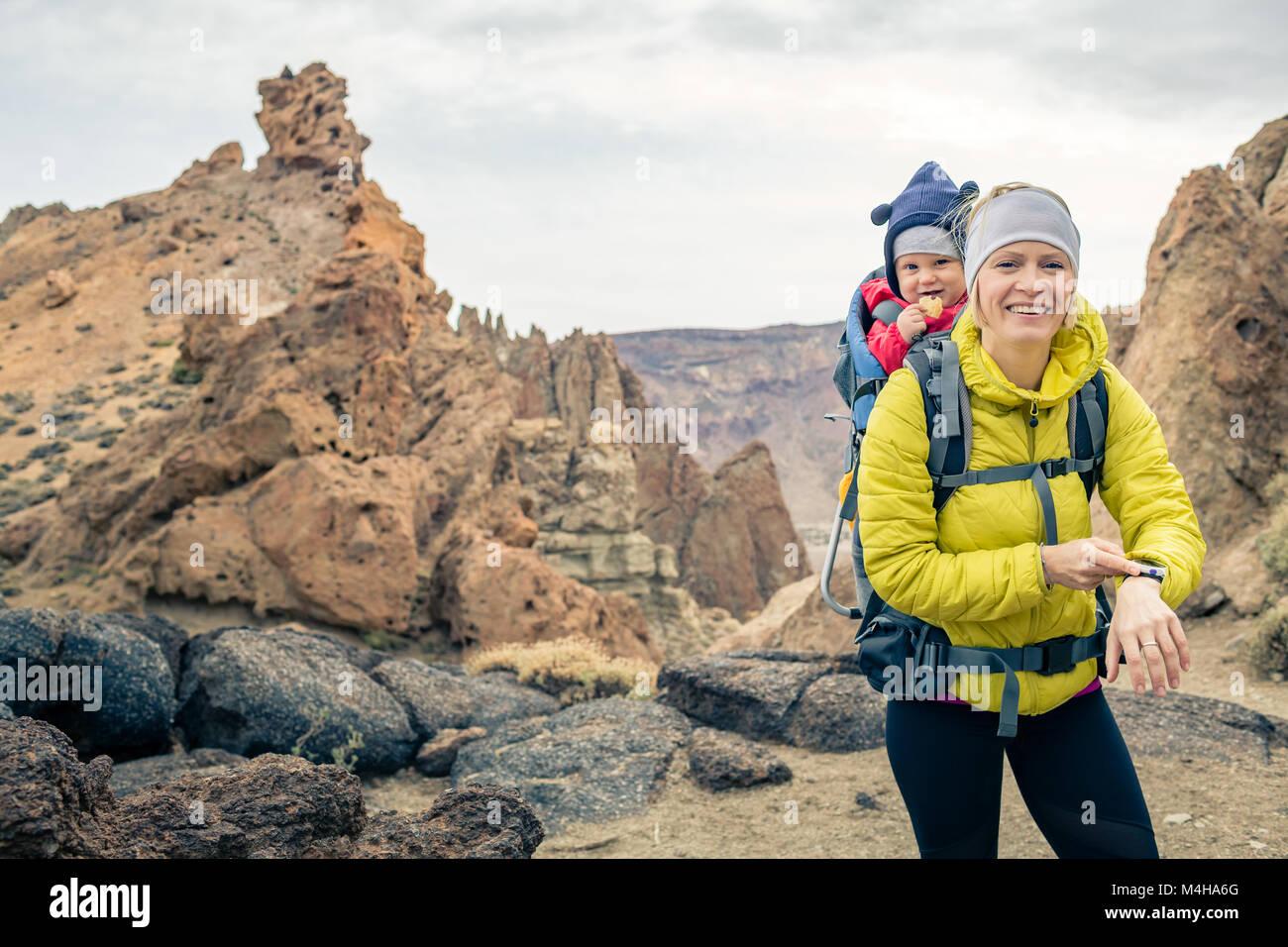 Super Mutter mit Baby boy in Rucksack reisen. Wandern Abenteuer mit Kind auf Herbst Familie Reise in die Berge. Stockbild