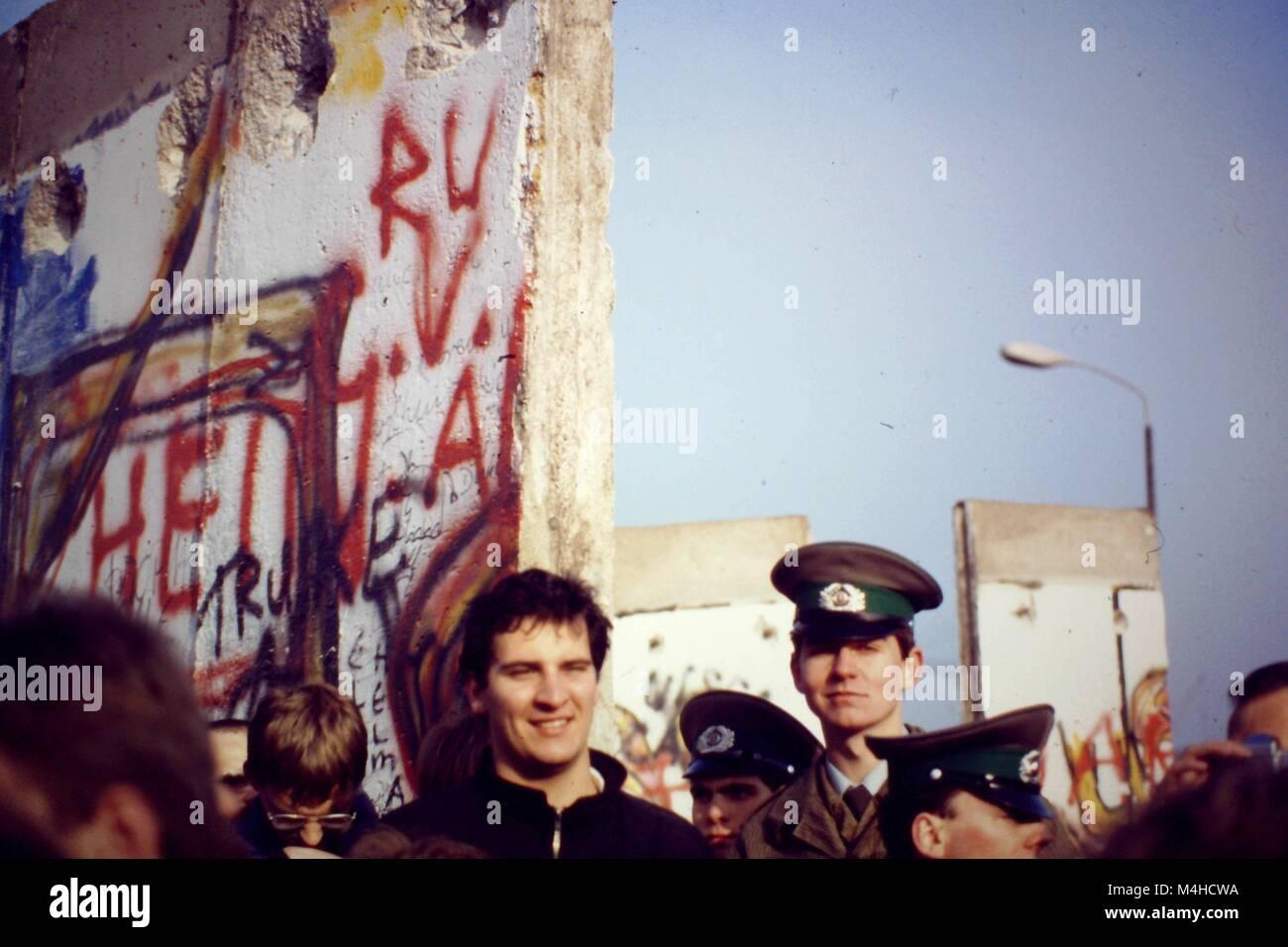 Ein junger Mann und die Mitglieder der Volkspolizei stehen vor der geöffneten Mauer in Berlin. Stockbild