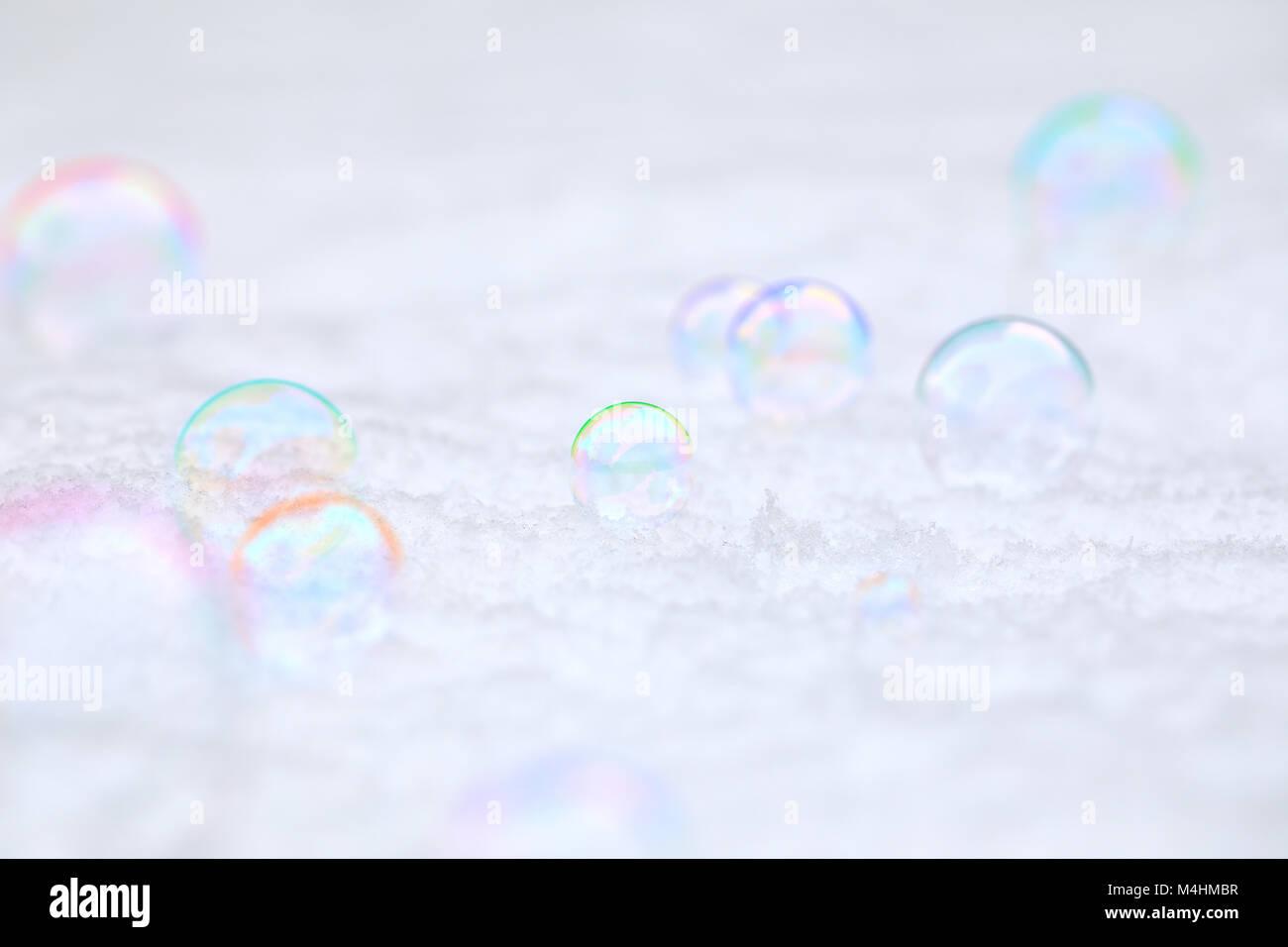 Blasen im Schnee mit einem Regenbogen an Farben und schillernden und transluzente Effekte Stockfoto