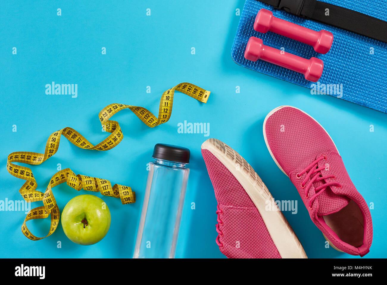 Sneakers mit Maßband auf cyan blau unterlegt ist. Zentimeter