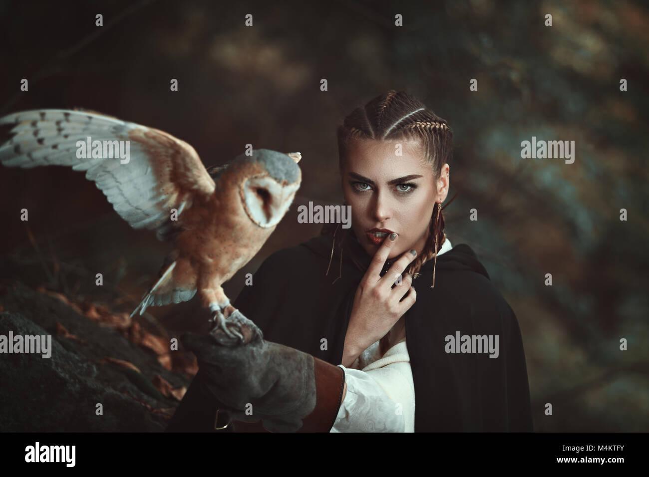 Frau mit schleiereule auf ihren Arm. Wald Hintergrund Stockfoto