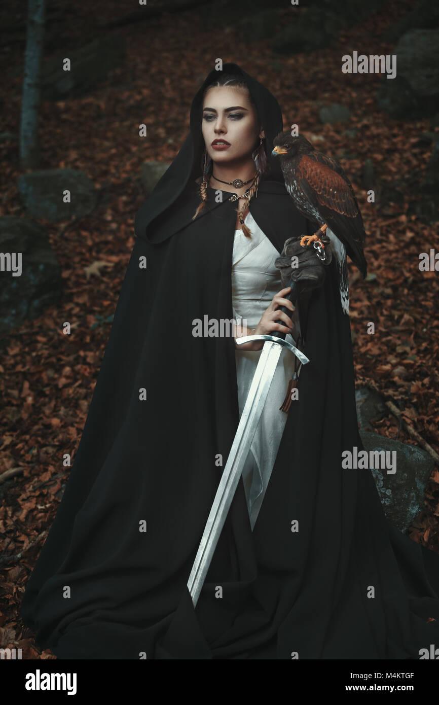 Stolz mit Kapuze Frau mit Schwert und Hawk. Wald Hintergrund Stockfoto