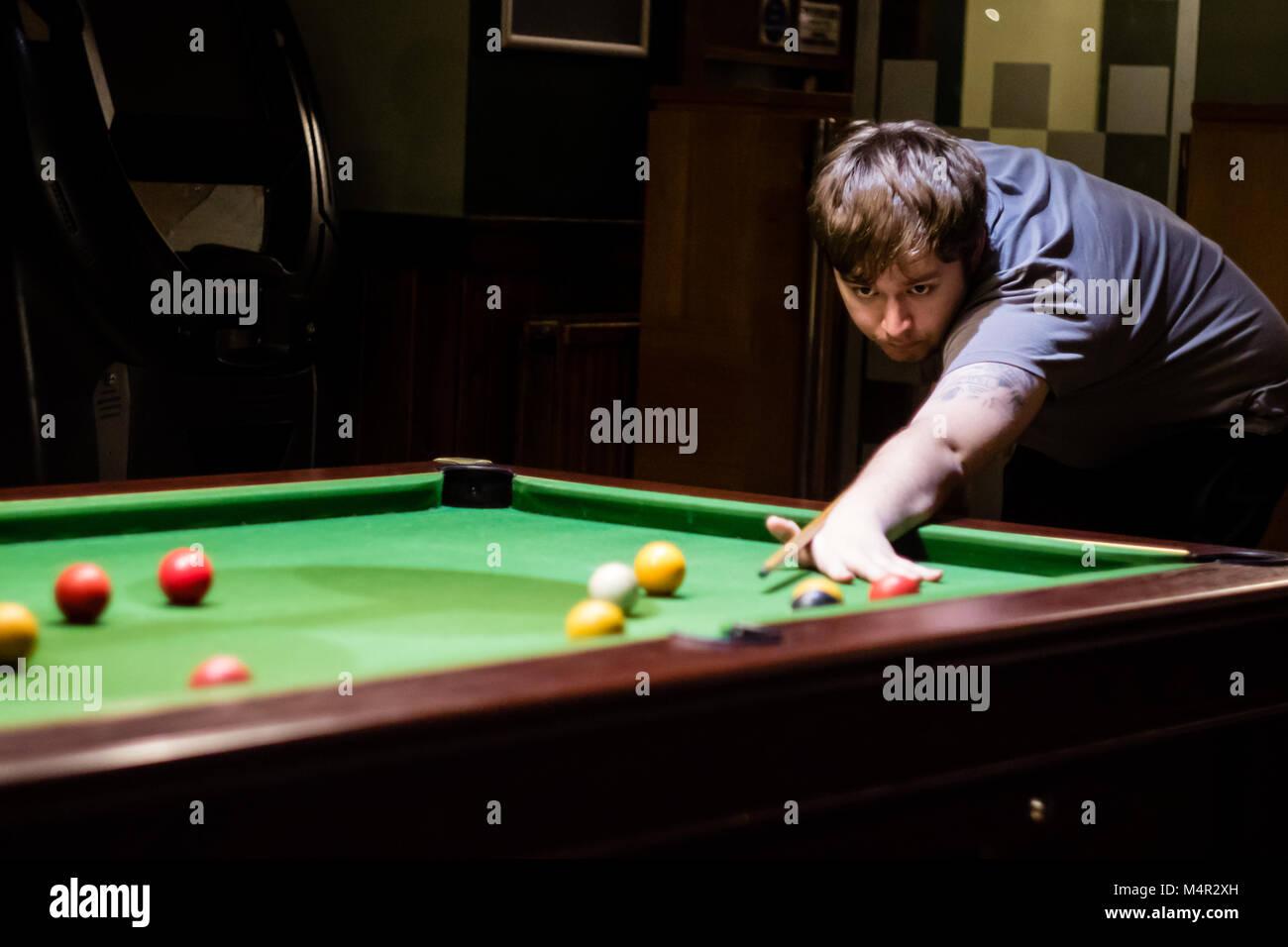 Ein Mann der Vorbereitung eines pool Shot, von vorne zu spielen Stockbild