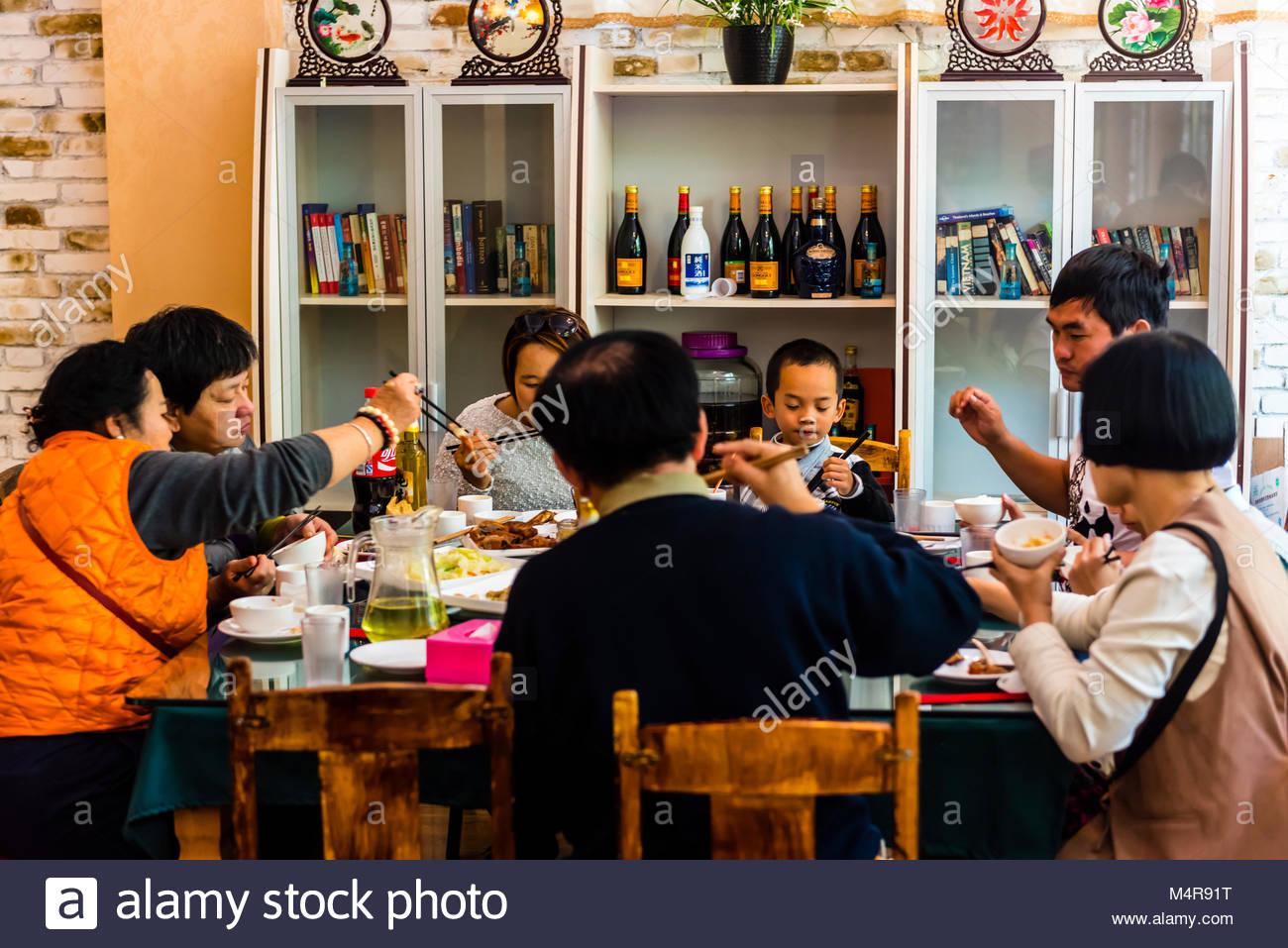 Eine Familie beim Mittagessen im Restaurant Mishi, Lijiang, Provinz Yunnan, China. Stockbild