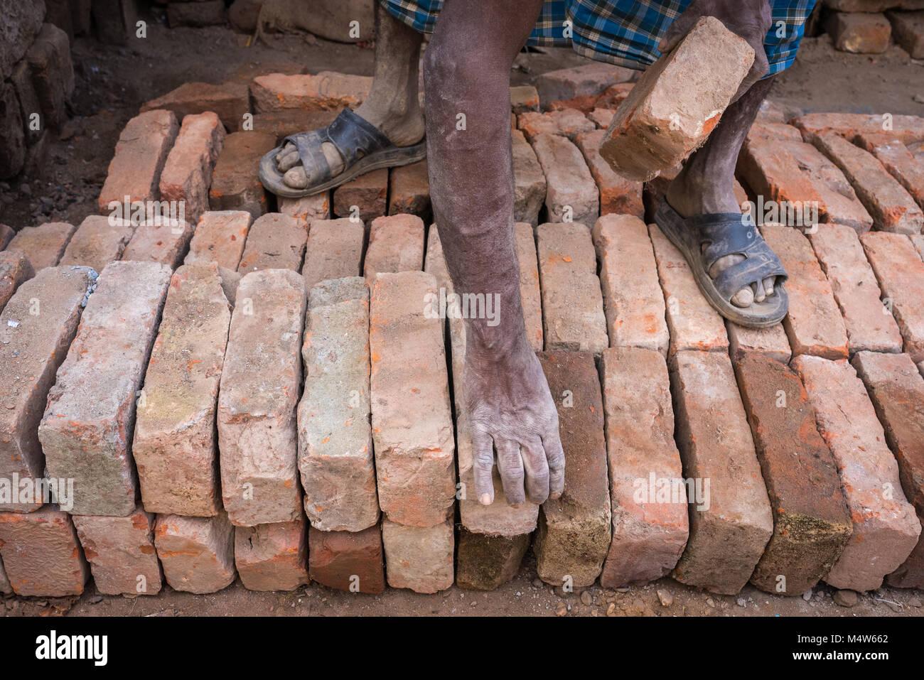 Ein Mann Stapeln von Ziegelsteinen in Varanasi, Indien. Stockbild