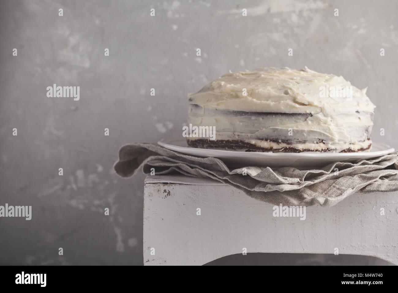 Eine ganze (Karotte) Kuchen mit Weiß Creme auf grauem Hintergrund. Festliches dessert Konzept. Stockbild