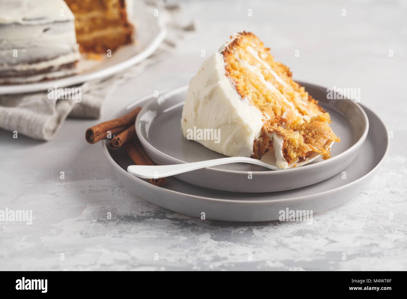 Stück Karotte hausgemachte Kuchen mit Weiß Creme auf grauem Hintergrund. Festliches dessert Konzept. Stockbild