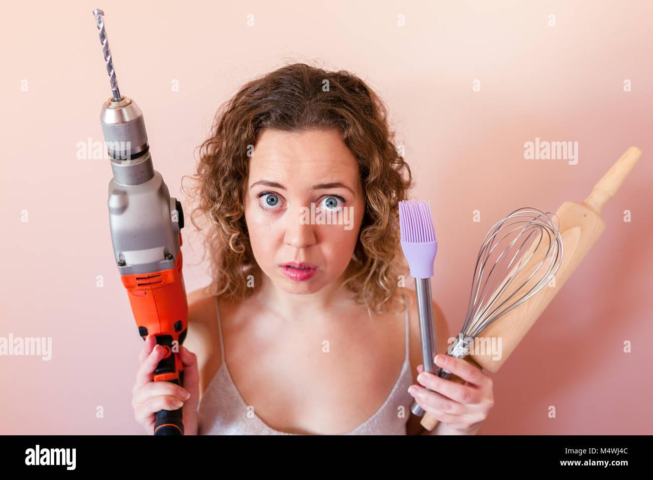 Schöne lockige Frau mit Mann driller und Küchengeräte. Die Gleichstellung von Frauen und Männern, Stockbild