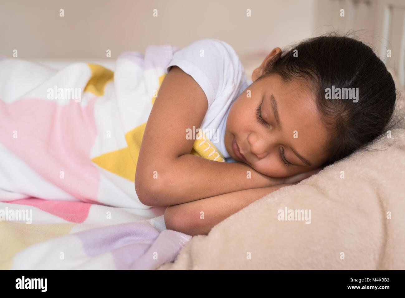 Jungen kleinen asiatischen Mädchen schlafen liegend auf Bett in ihrem Schlafzimmer. Schlaf Konzept Stockbild