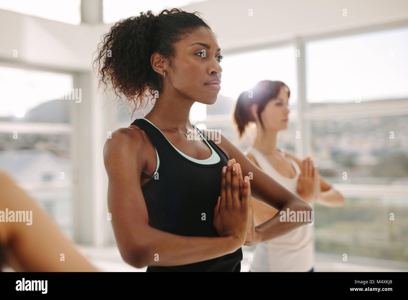 Frauen Yoga zusammen, stehend mit Händen in Namaste Geste. Frauen stehen im Yoga pose im Fitnessstudio. Stockbild