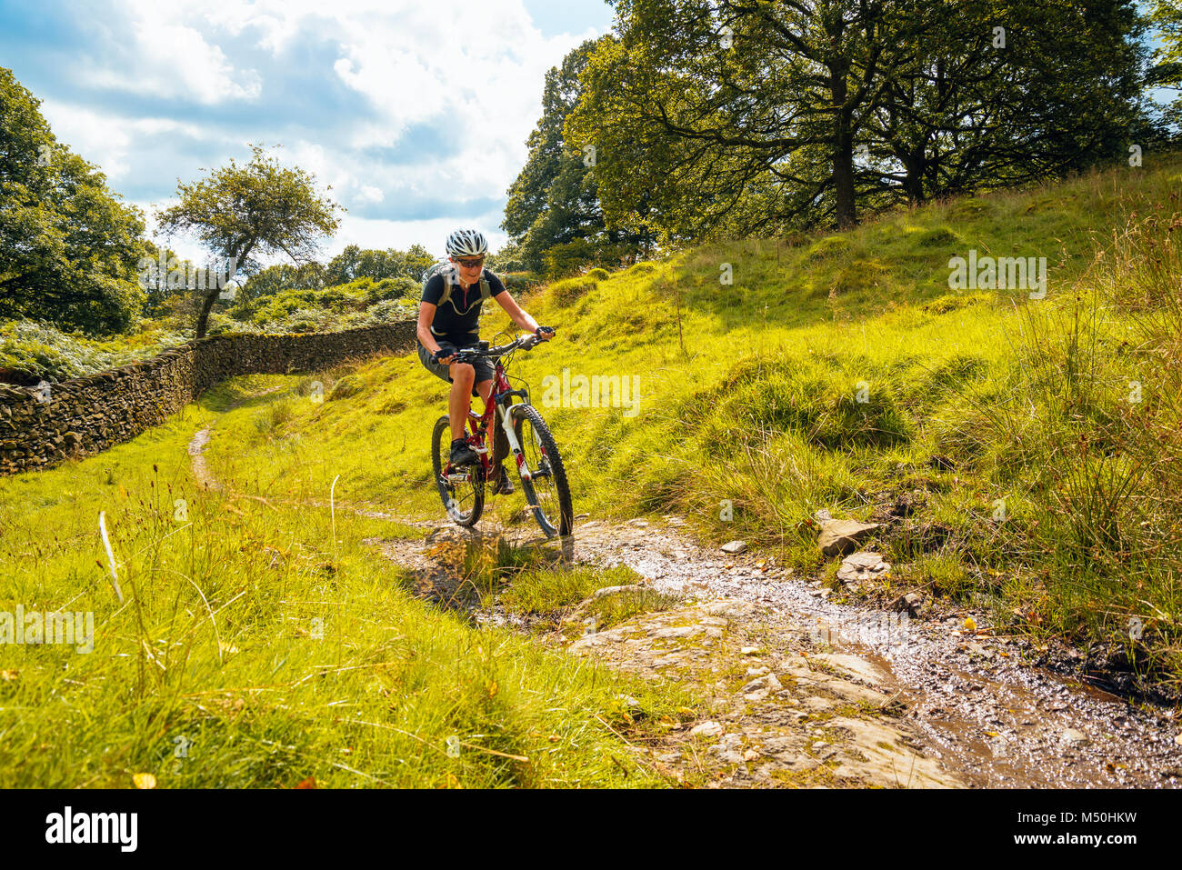 Weibliche Mountainbiker auf der Strecke in der Nähe Winster im englischen Lake District Stockbild