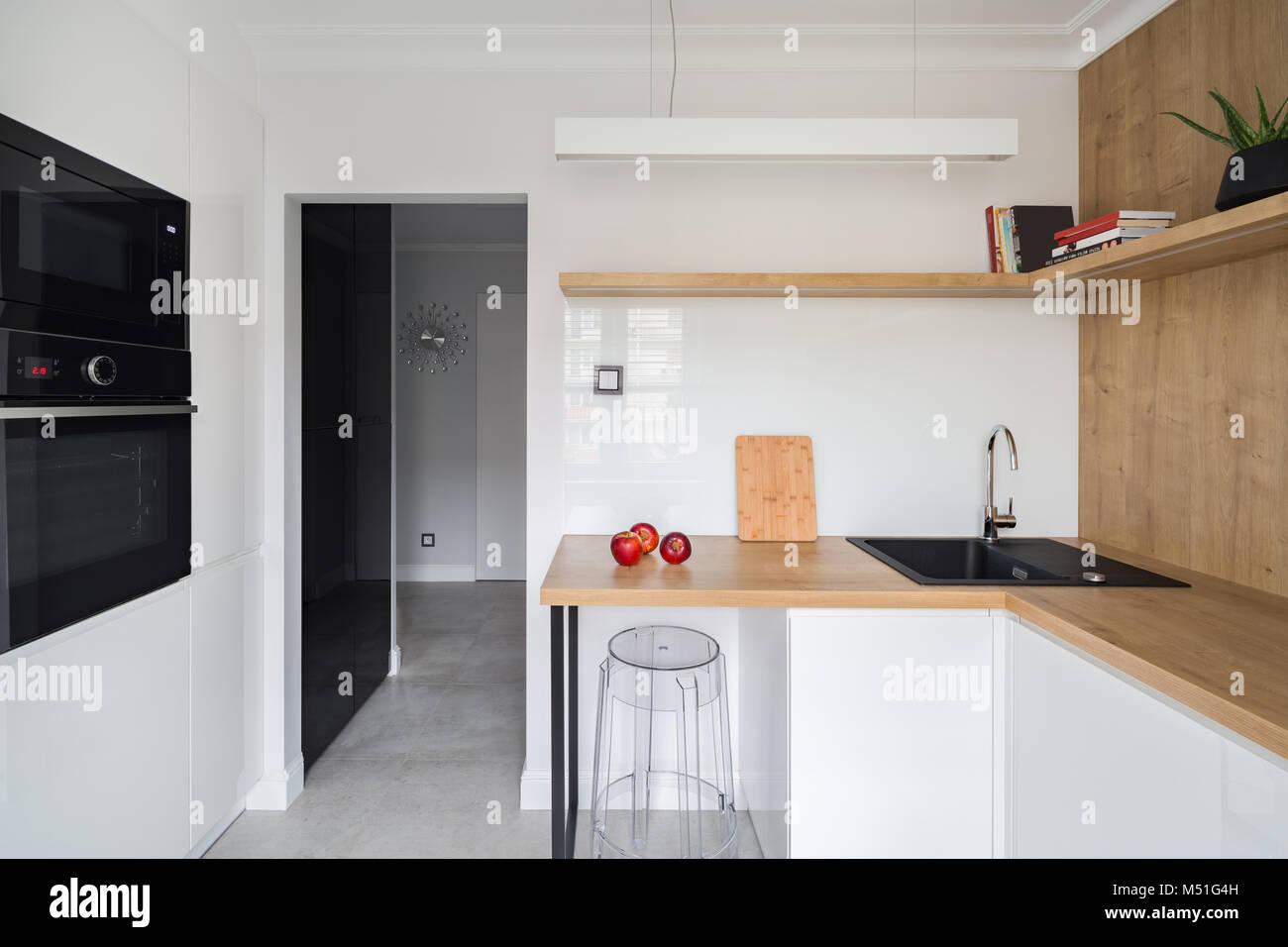 Moderne, weiße Küche mit Holz- Arbeitsplatte und transparente Stuhl ...