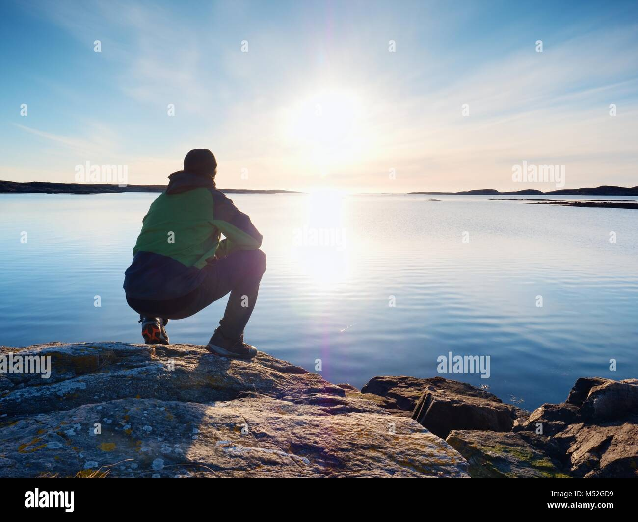 Einsamer Mann, Wanderer sitzt alleine an der felsigen Küste und genießen den Sonnenuntergang. Blick über die felsige Klippe zum freien Ozean Stockfoto