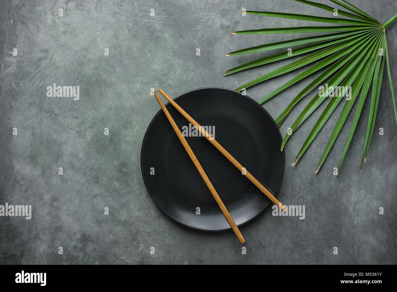 Schwarze leere Platte mit braunen Bambus Stäbchen Pal Baum Blatt auf ...