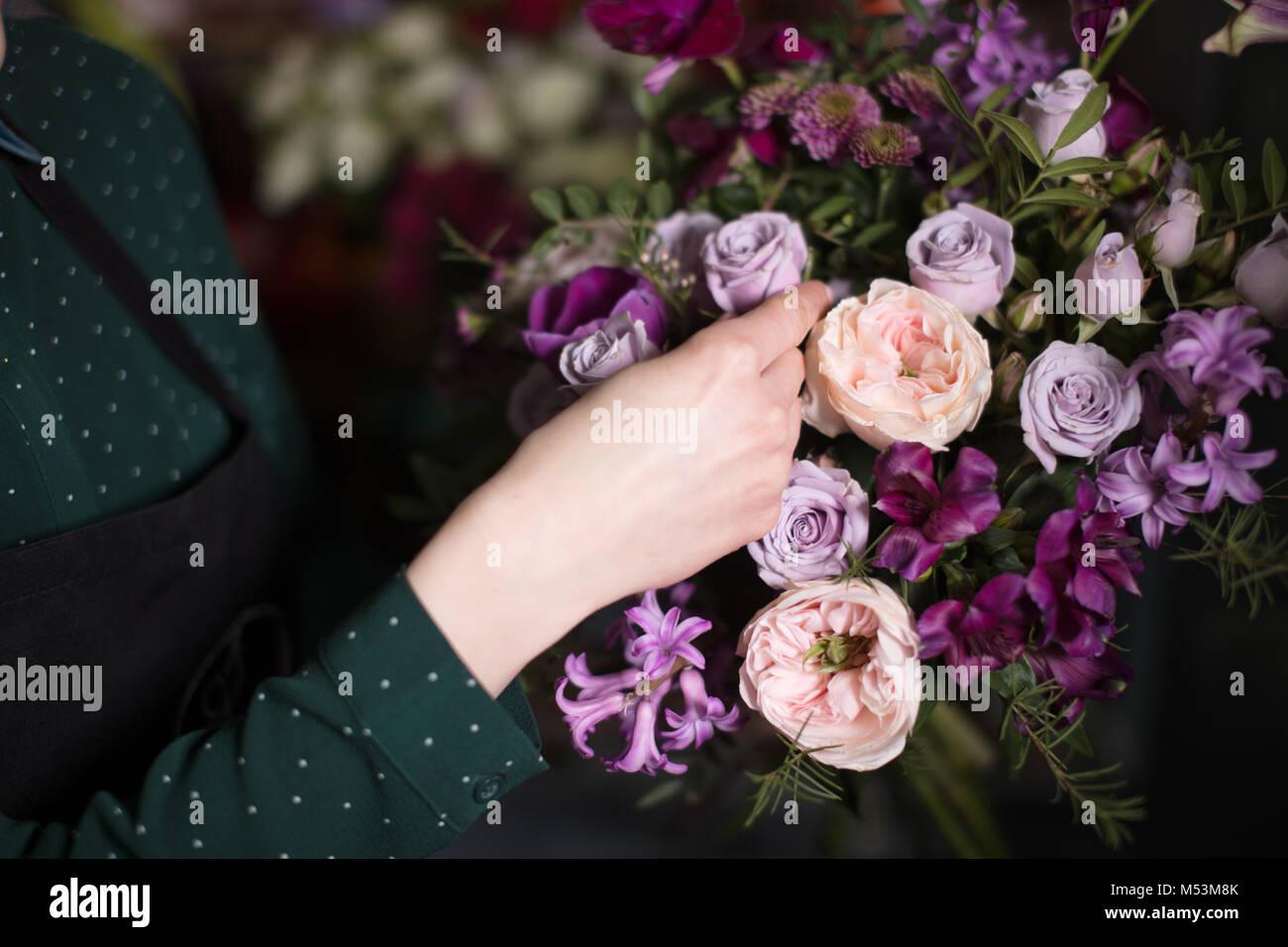 Junge Verkäufer berühren wunderschöne Rosen im Shop Stockbild