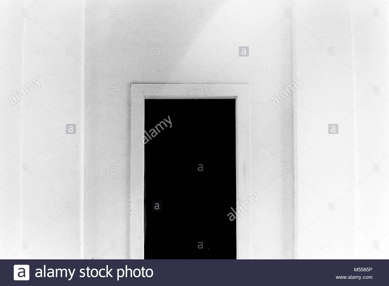 Schwarze Tür auf der weißen Wand Stockbild