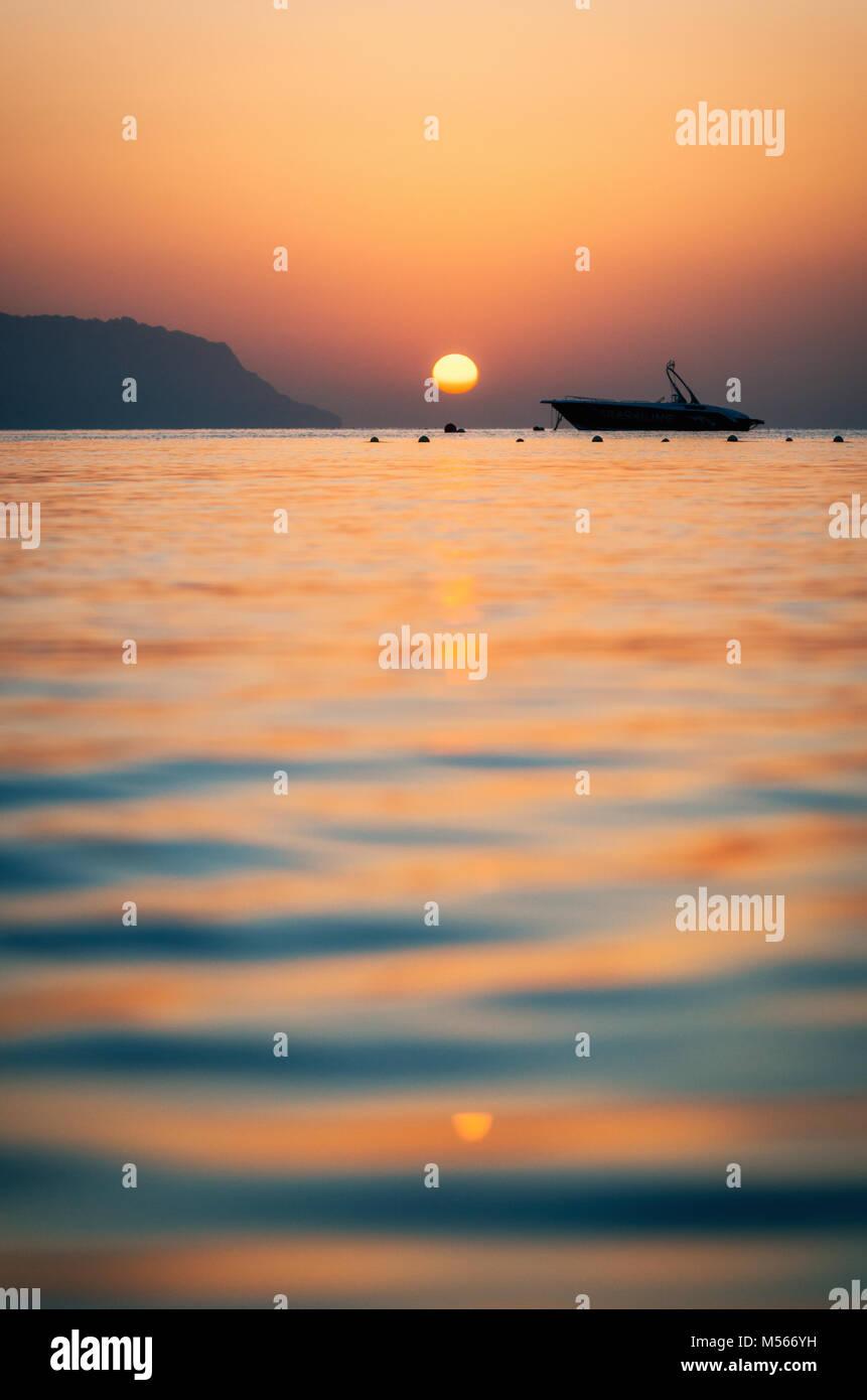 Warme Bunte sunrise auf die Insel Tiran mit Kräuselung auf Meer und Boot in Sharm El-Sheikh, Ägypten. Stockbild