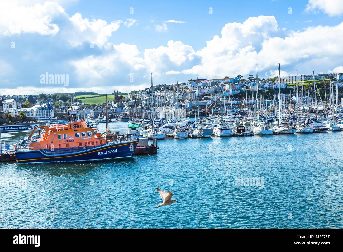 Ein rnli Lifeboat mooed im Hafen von Brixham mit anderen Booten. Stockbild