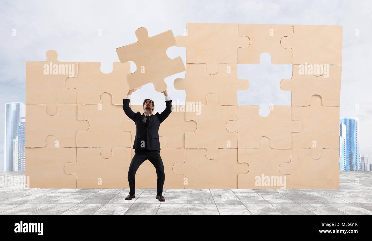 Geschäftsmann mit einem Stück des Puzzles. Das geschäftskonzept Erstellen Stockbild