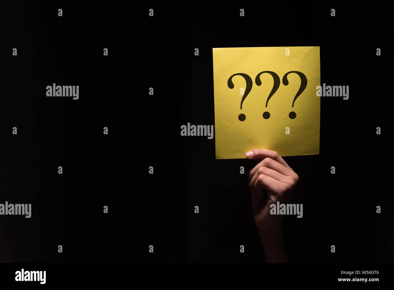 Hand mit einem gelben Papier mit Fragezeichen in einen dunklen Hintergrund Stockbild