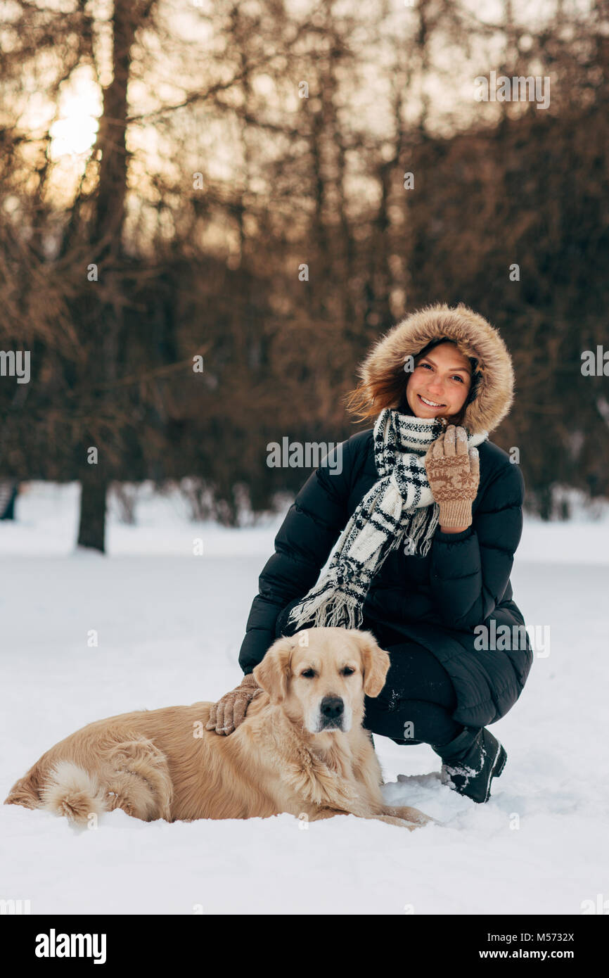 Bild der Frau auf Spaziergang mit Hund auf dem Hintergrund der Bäume im Winter Stockbild
