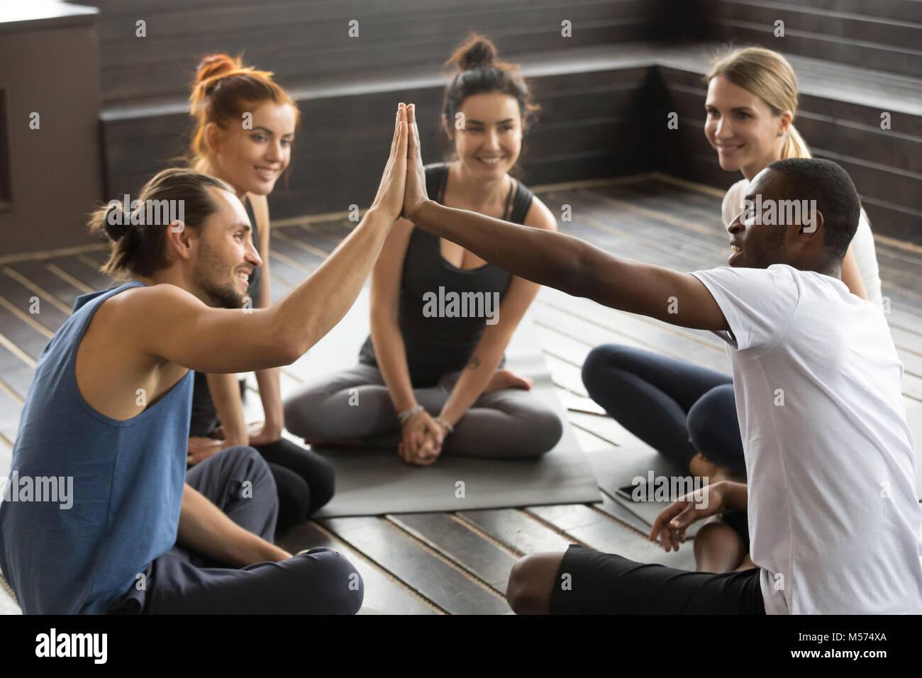Lächelnd diverse Yoga Teammitglieder hohe - fünf bei Gruppe Trai Stockbild