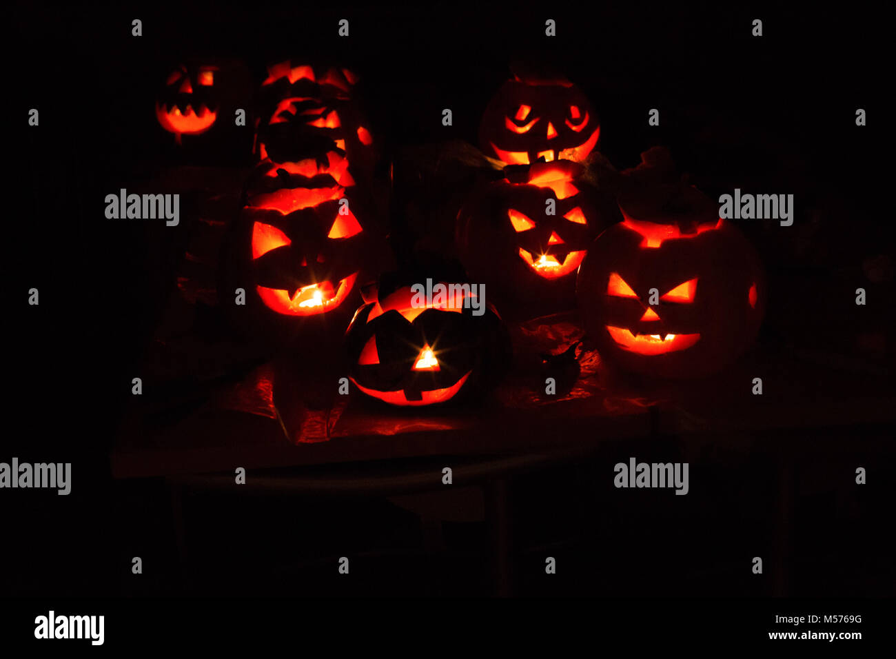 Kürbis - Jack, schrecklich, unheimlich, Nacht, schwarz, Leuchten, Lampe, Kerze, rot hinterlegt, in der Dunkelheit, Stockbild