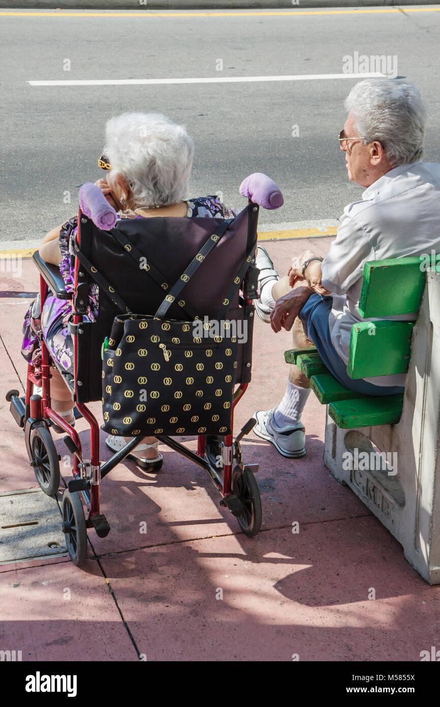 Miami Beach Washington Avenue senior älterer Mann Frau paar Rollstuhl deaktiviert Behinderte Gesundheit Stockbild