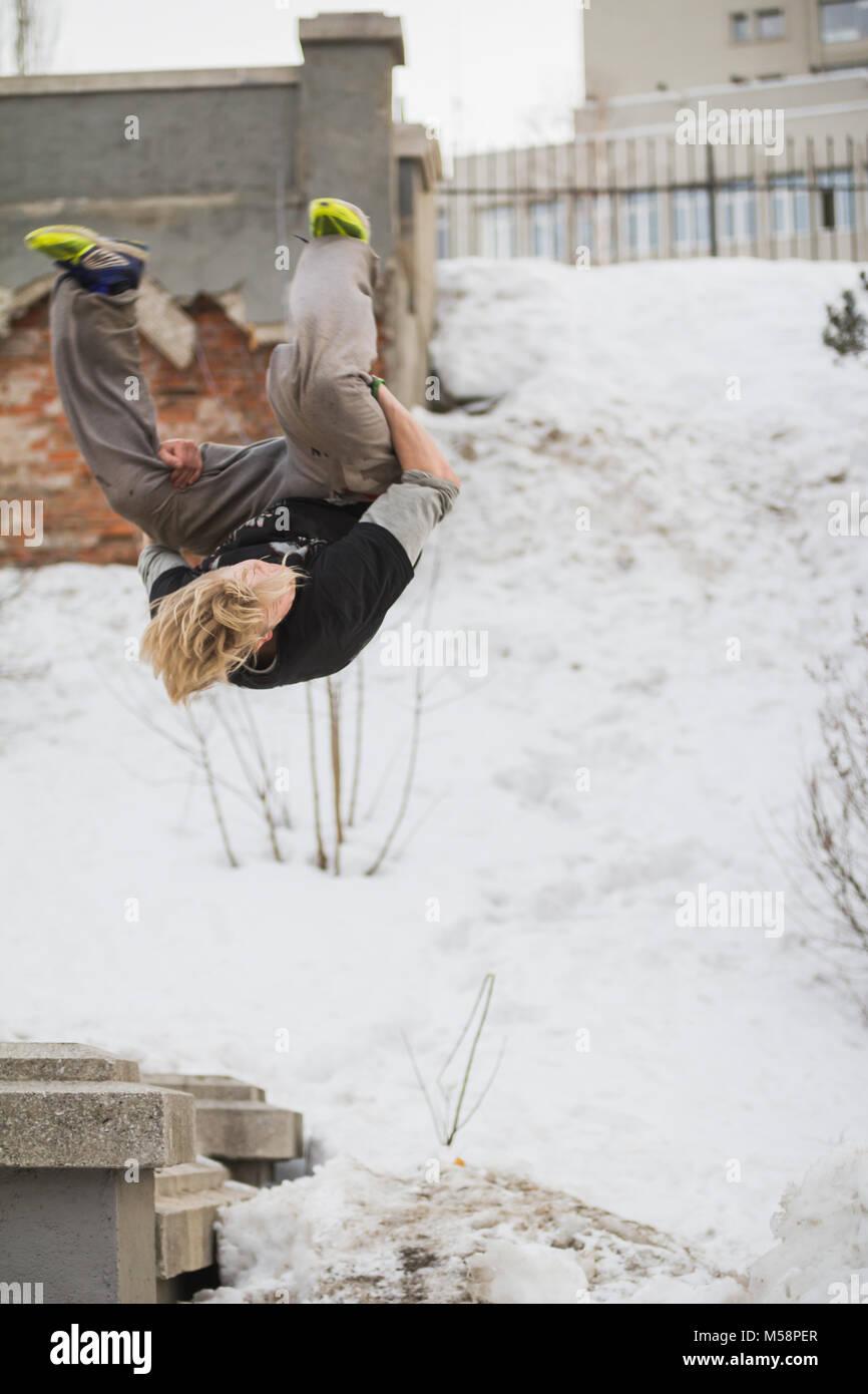 Teenager blondes Haar Kerl Ausbildung parkour Sprung Flip in den verschneiten Park Stockbild