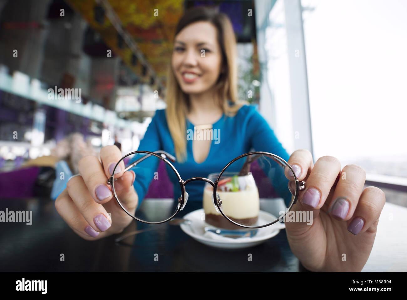 Hübsche junge Mädchen halten Gläser in den Händen im Cafe sitzen, Augenheilkunde Stockbild