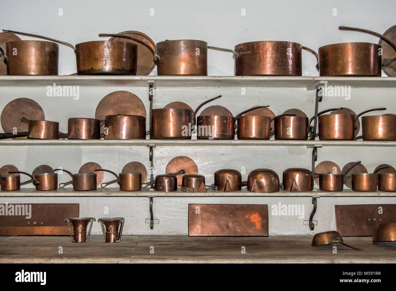 Alte Küchengeräte in Kupfer, verteilt auf drei Regale in der Küche ...