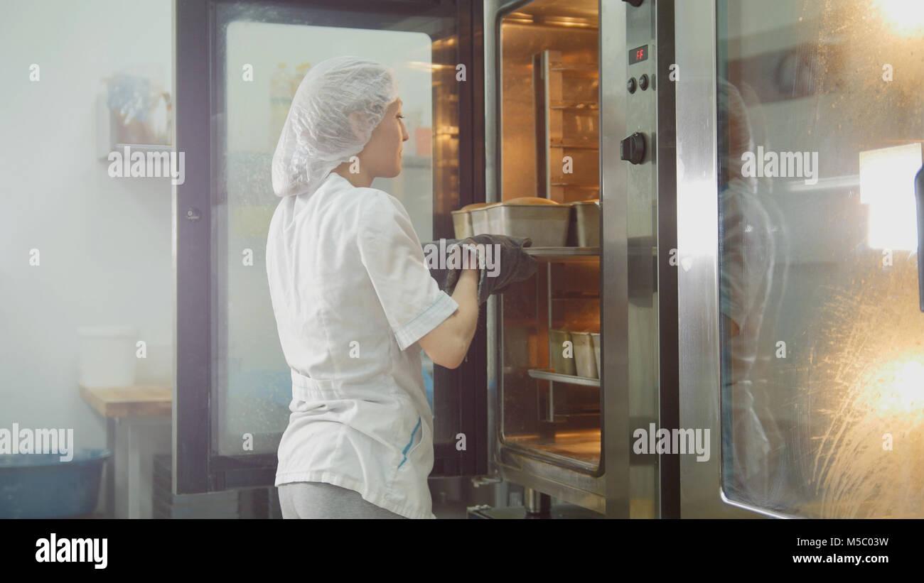 Weibliche backt auf die gewerbliche Küche - Frau setzt Backen im Ofen Stockbild