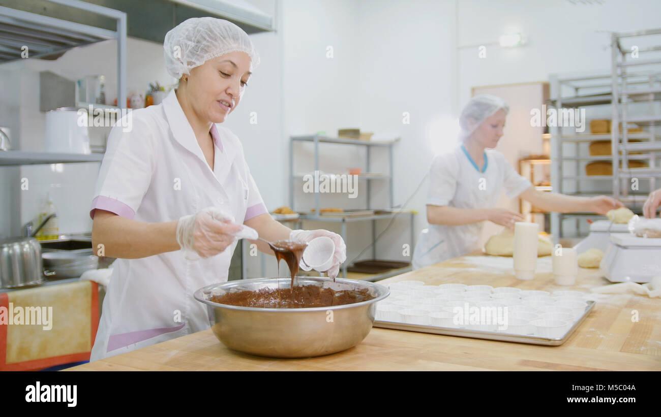 Weibliche baker mischt Schokoladencreme in Metall Schüssel und Kuchen Stockbild