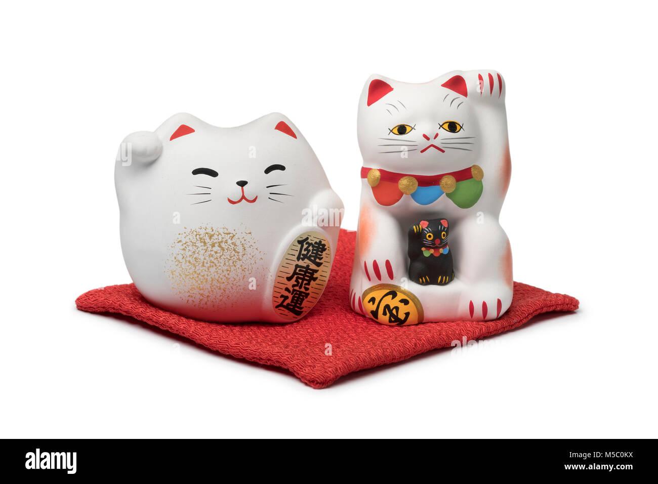 Japanische Maneki Neko, lucky Katzen auf einem roten Kissen auf weißem Hintergrund Stockbild