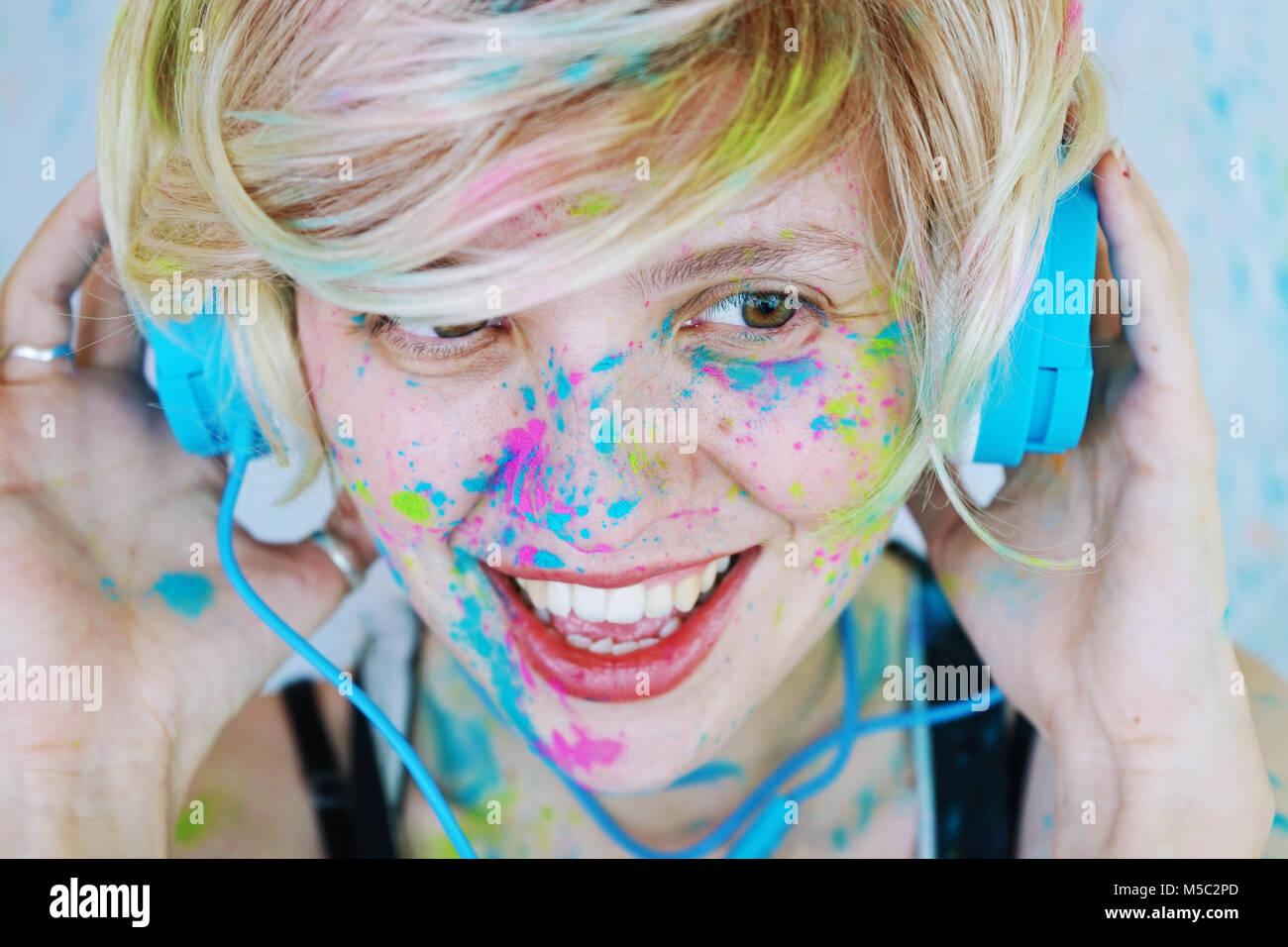 Junge Frau mit Farbe im Gesicht ist das Hören von Musik Stockbild