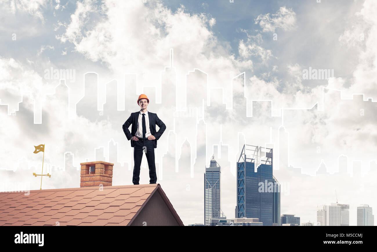 Ingenieur-Mann steht auf Dach und wegsehen. Mixed-media Stockbild