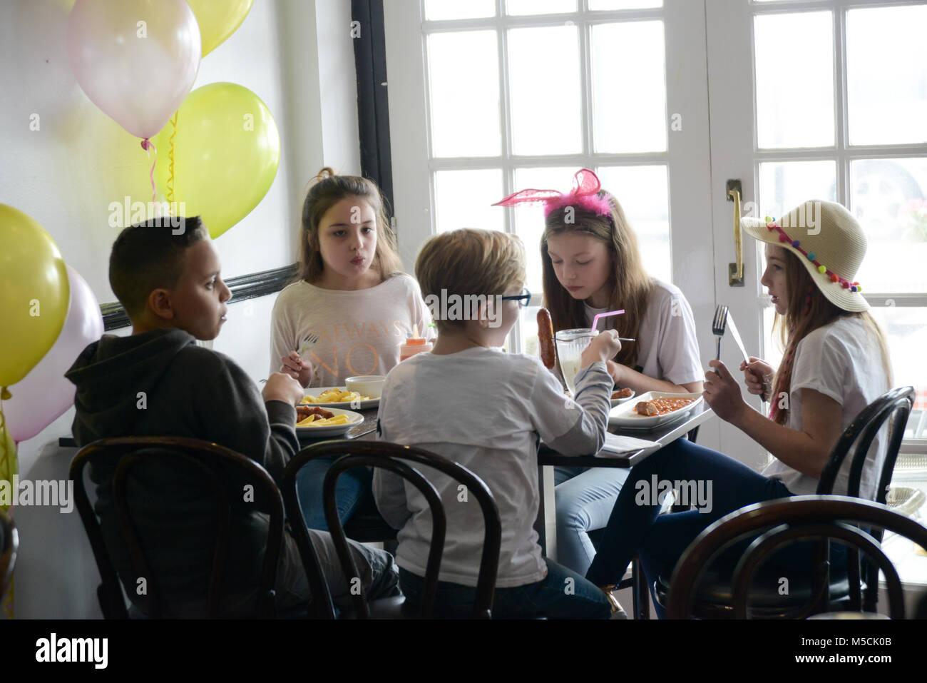 Fünf junge Kinder sitzen auf einer Party Tisch essen gebratene Nahrung und trinken Milchshakes - es gibt Ballons Stockbild