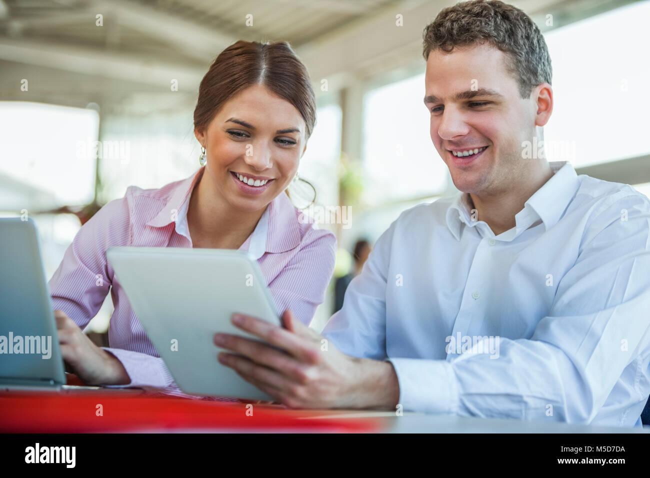 Lächelnden jungen Geschäftsleuten mit Technologien im Büro Stockbild