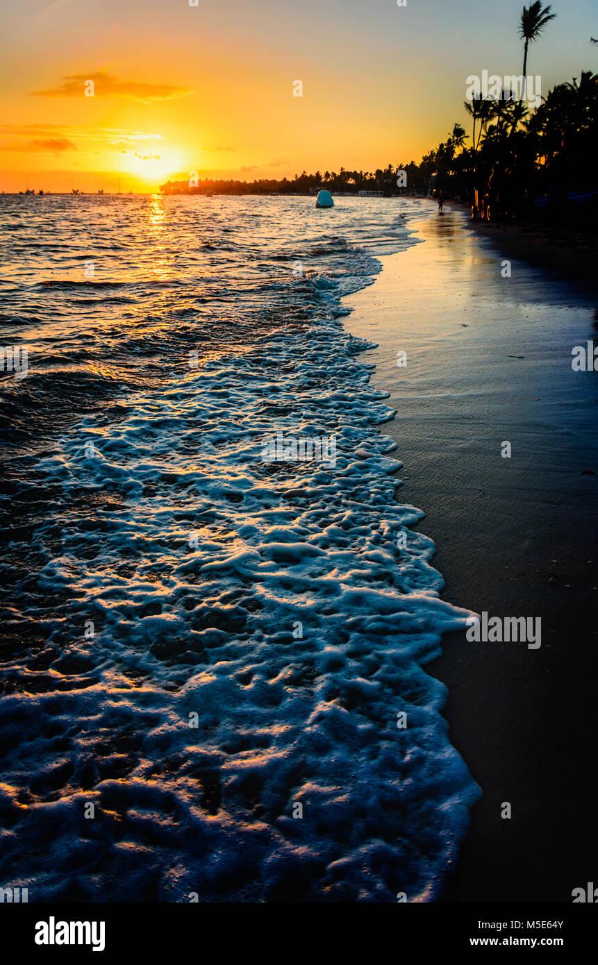 Sonnenaufgang auf dem Meer, Weißes Meer Schaum, Spiegelbild im Wasser, glänzenden Sand und Silhouetten Stockbild