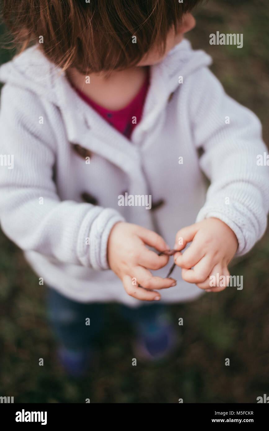 Ein Kleinkind Mädchen hält einen Wurm in ihre Hände an einem kühlen Frühlingstag. Stockbild