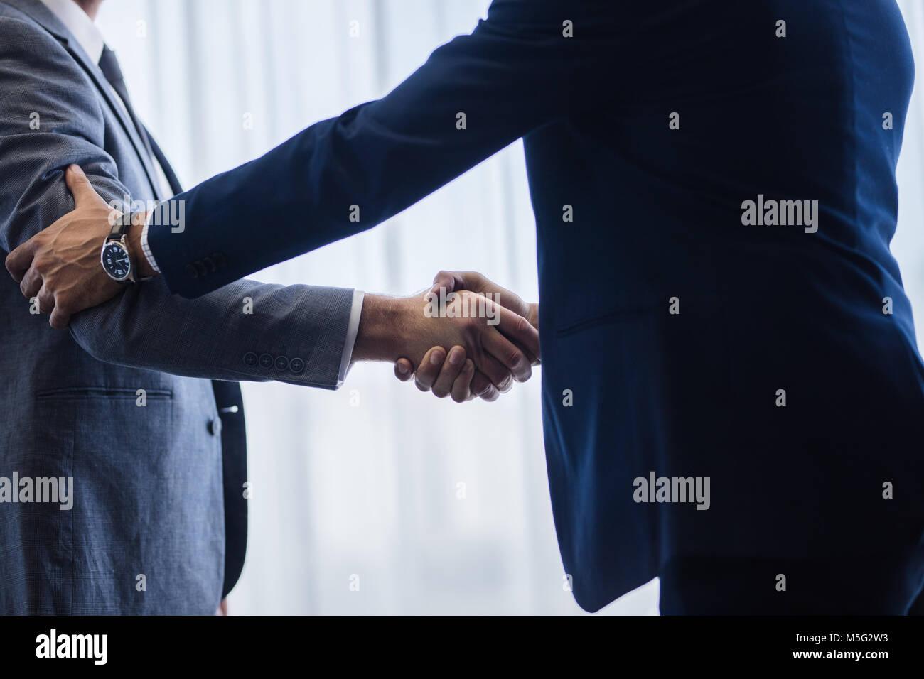 Anspruchsvolle Geschäftsleute Händeschütteln mit einander nach einem Abkommen. Geschäftsleute, Stockbild