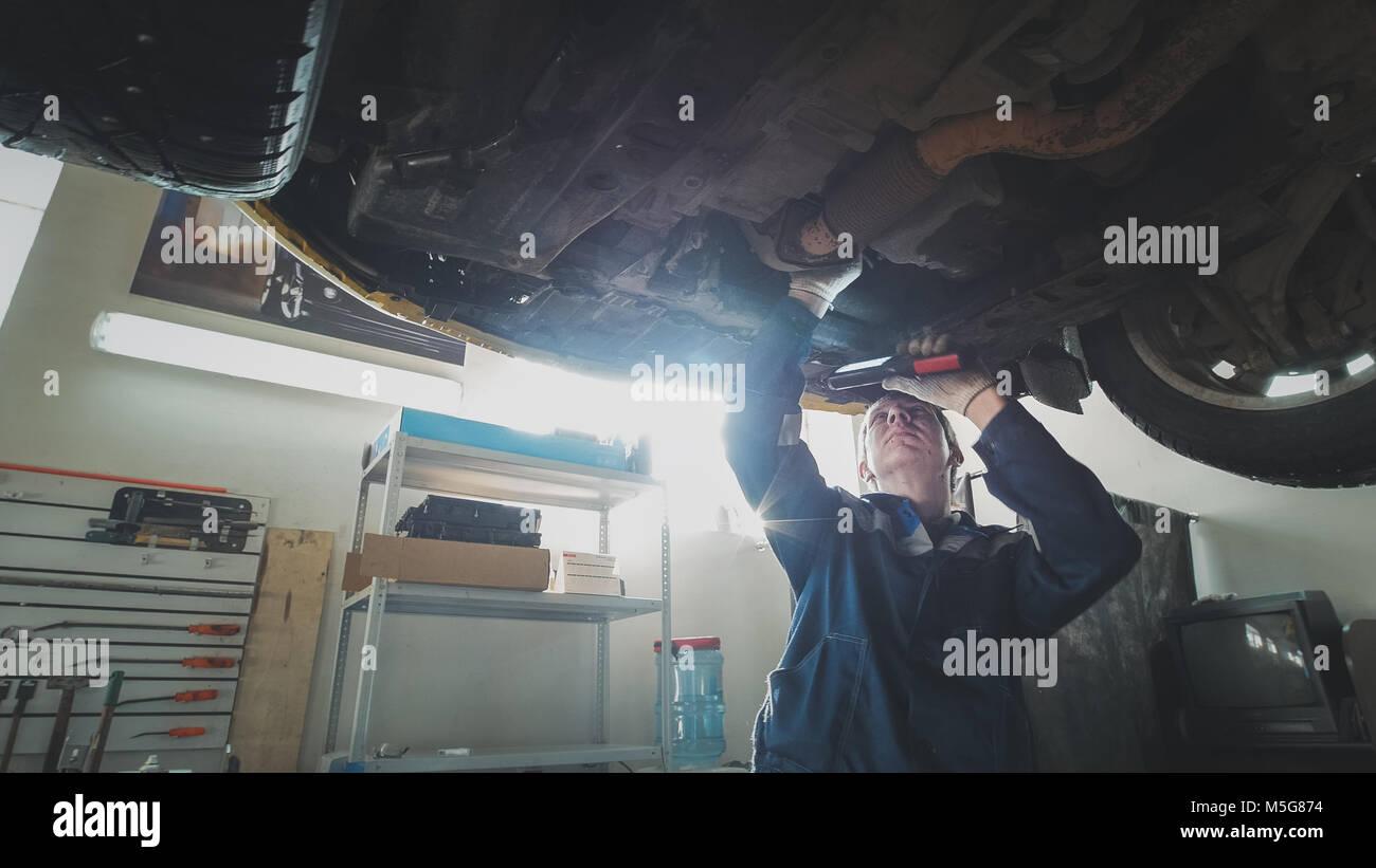 Mechanischer Auto Werkstatt - ein Mechaniker prüft die Aussetzung der Auto, Weitwinkel Stockbild