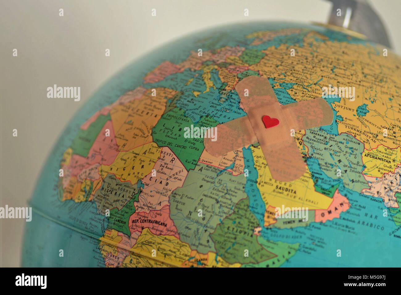 Welt mit Gips mit Herz - Solidarität und Hilfe für die bedürftigen Ländern Konzept Stockbild