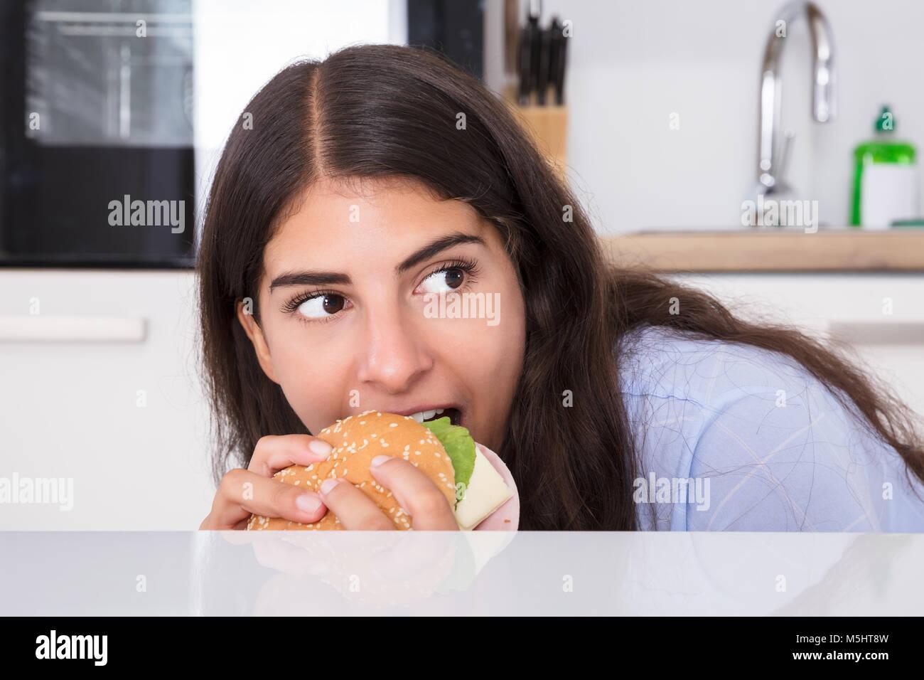 Nahaufnahme einer jungen Frau heimlich Essen Burger zu Hause Stockbild