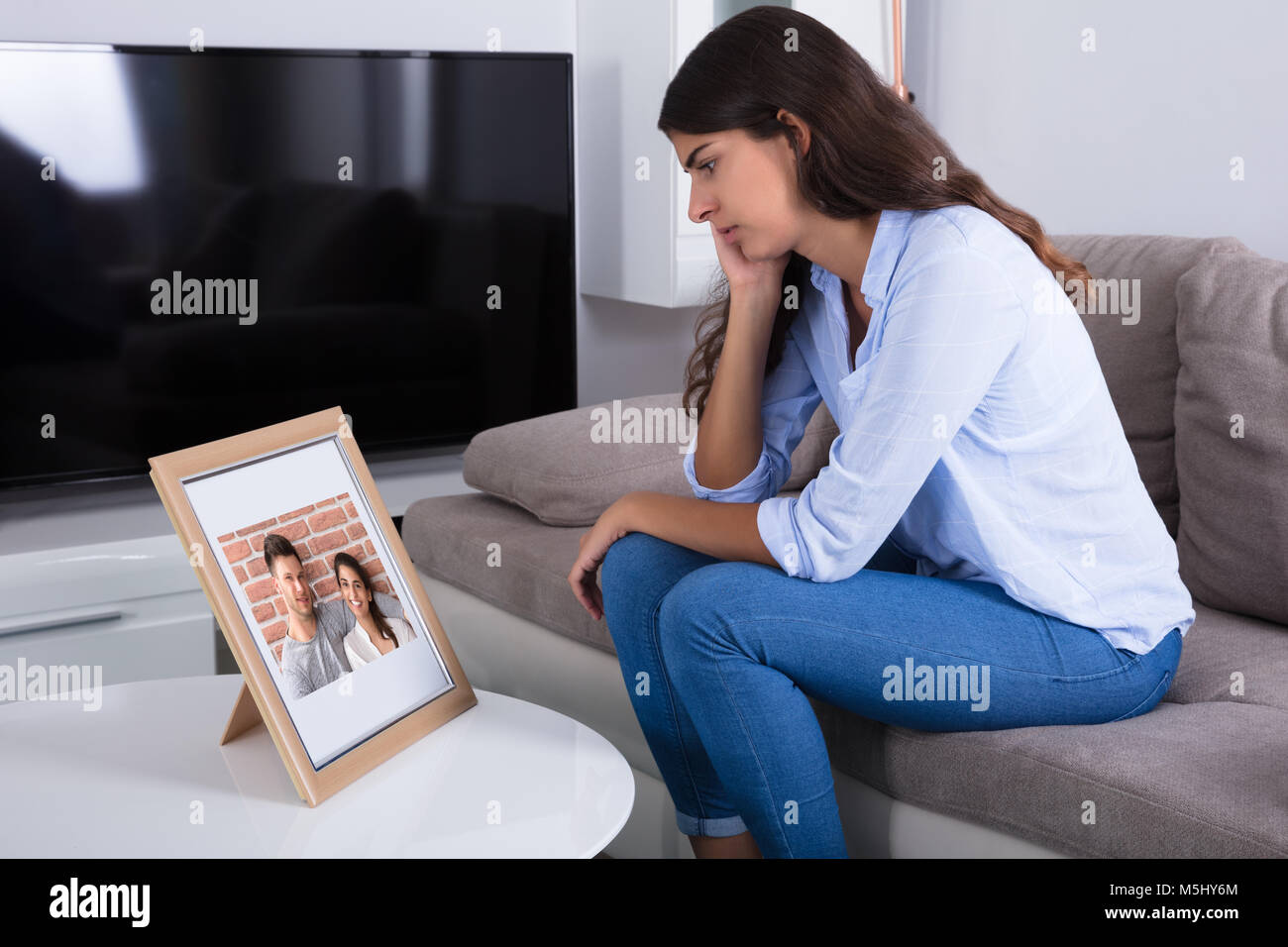 Traurige Frau mit Bilderrahmen von Paar in Liebe zu Hause Stockfoto ...