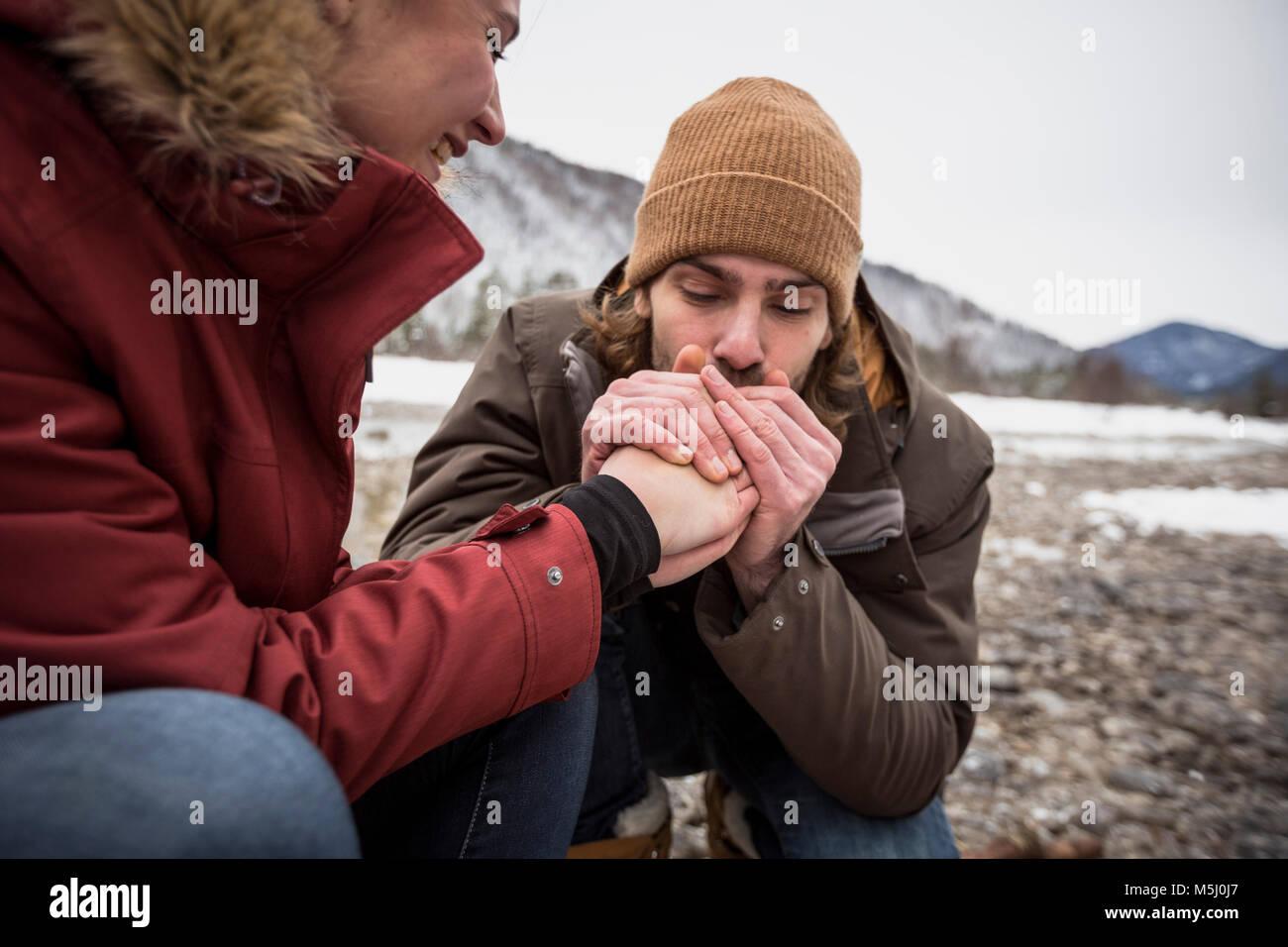 Paar auf eine Reise im Winter mit man wärmende Hände von Frau Stockbild