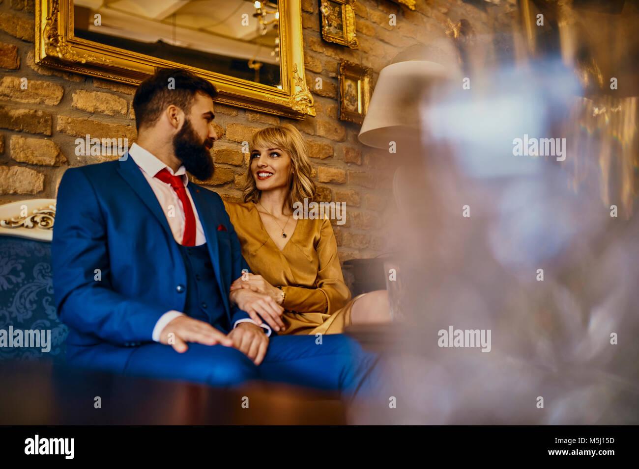 Elegantes Paar sitzt auf der Couch sprechen Stockbild