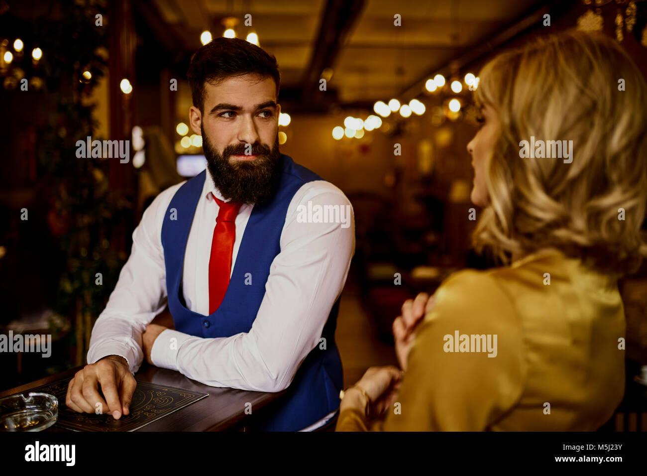 Modische junge Mann an Frau in einer Bar suchen Stockbild