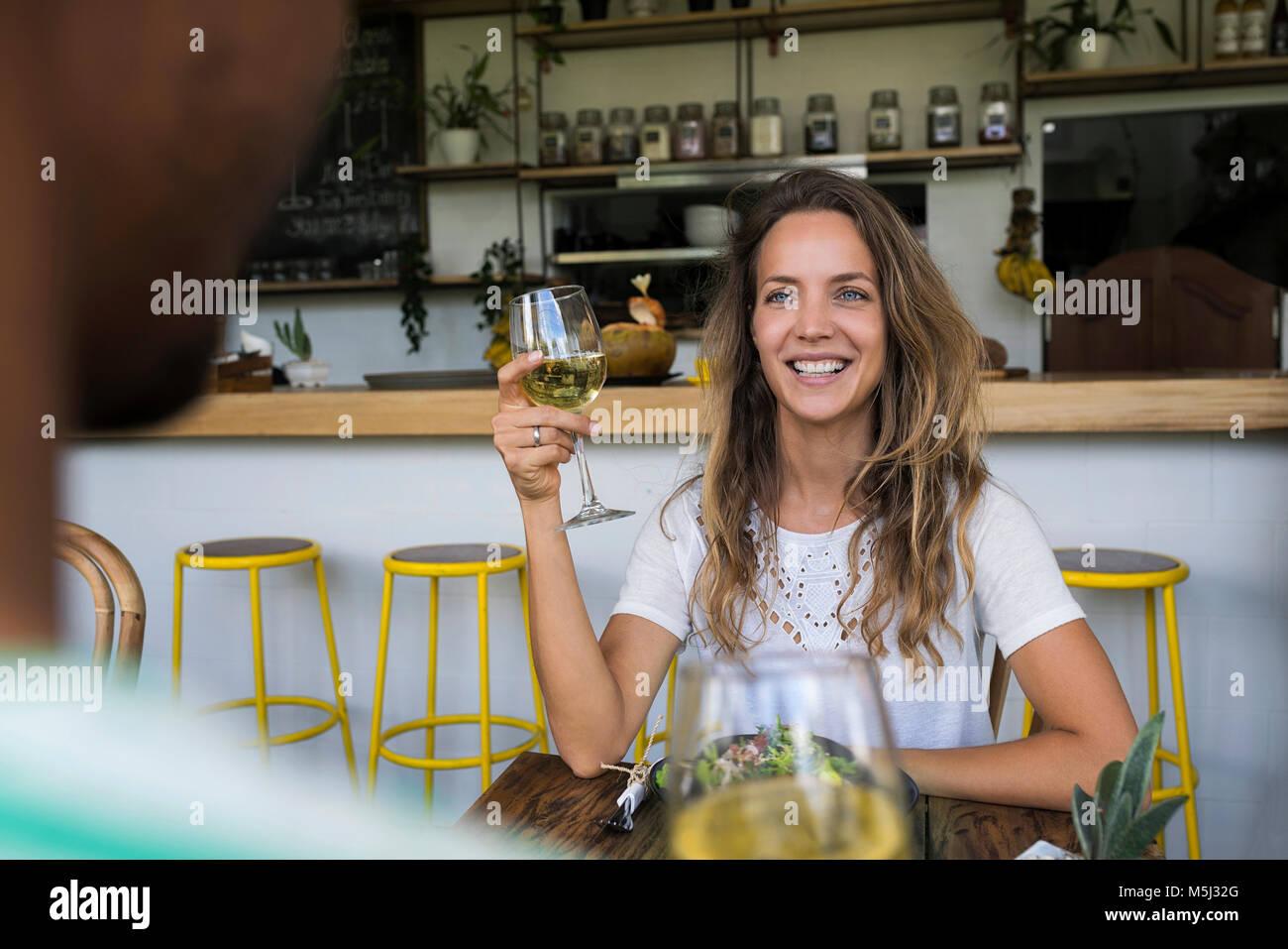 Lächelnde Frau mit einem Glas Wein bei man in einem Café auf der Suche Stockbild